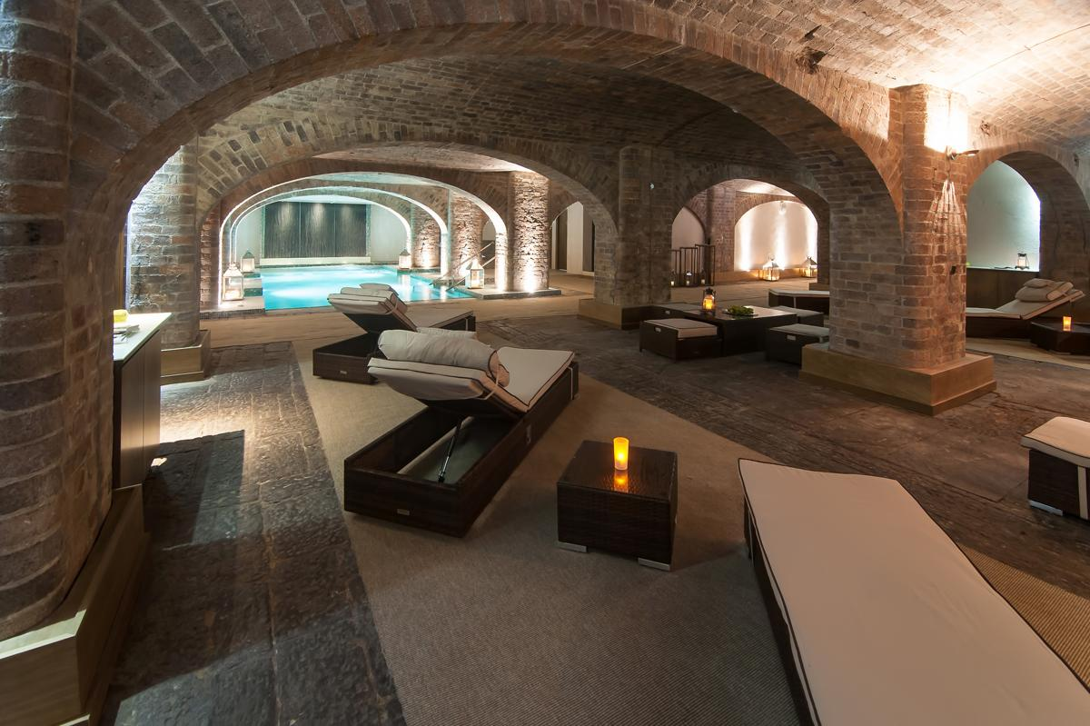 The five treatment rooms are encased in exposed brickwork arches and there is a Roman bath-style pool and an aqua thermal zone / Titanic Hotel Liverpool