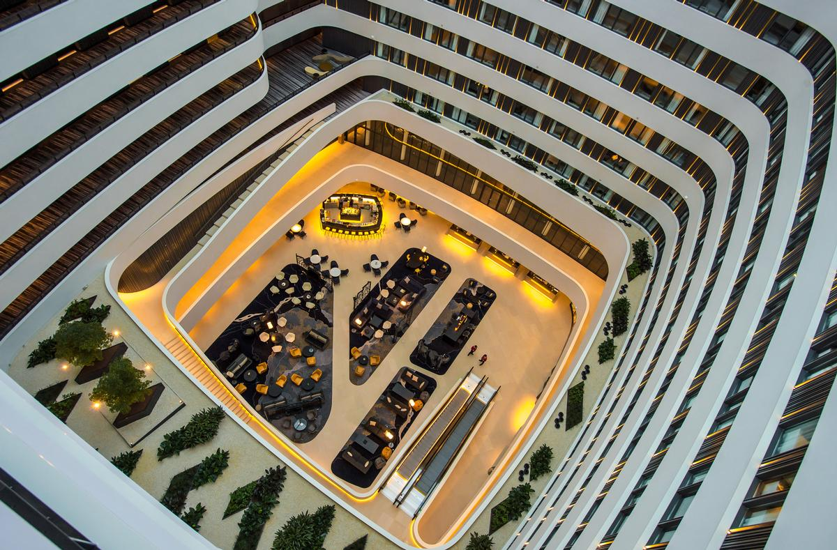 At the heart of the project is the 42-metre high atrium, which is sheltered by a huge glass roof / Hilton Hotels and Resorts