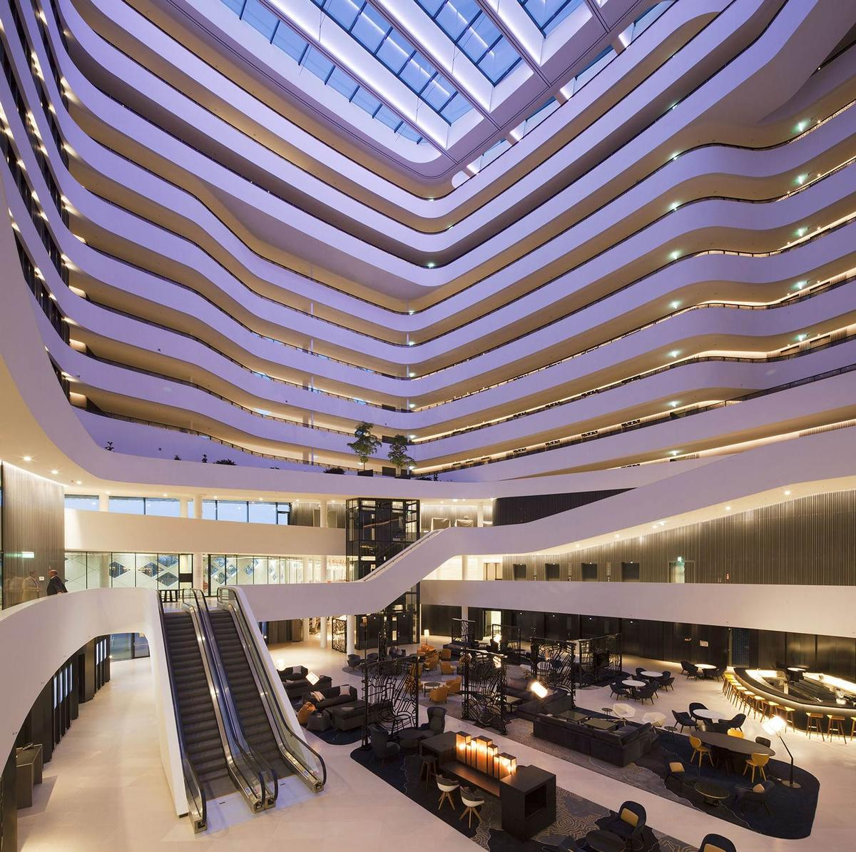 The atrium features 'islands' serving as multi-functional spaces, including a reception area, lounge and bar and indoor gardens.  / Mecanoo