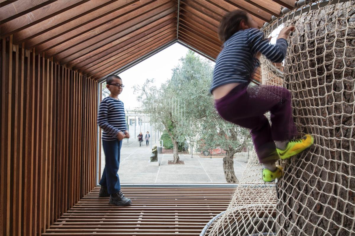 Wooden slats give the effect of transparencies across the structure / Amit Geron