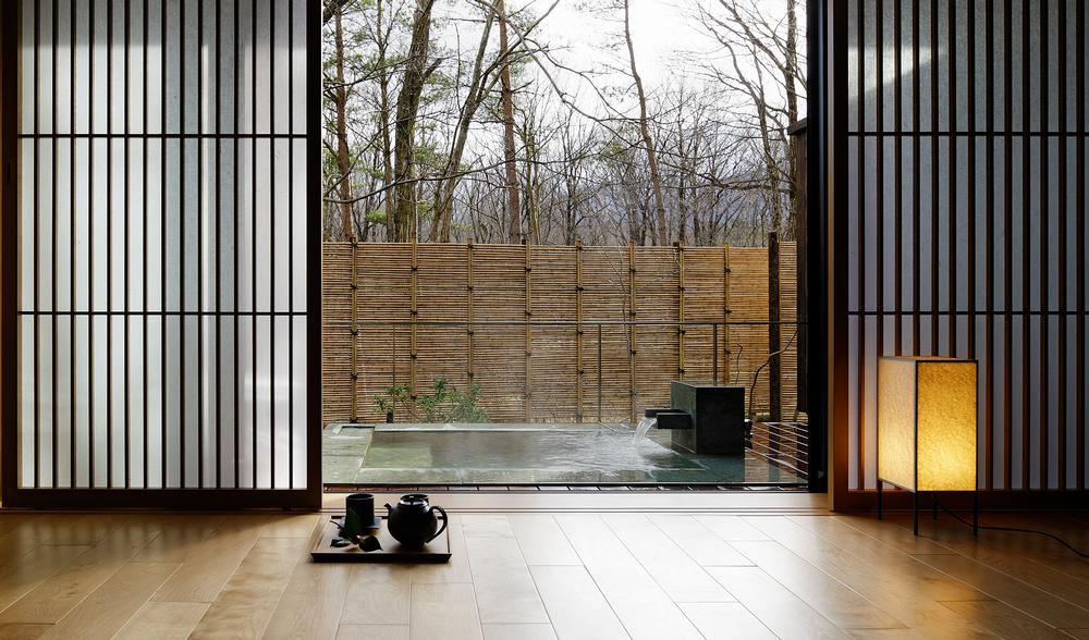 Large windows and folding doors provide views of the terraces and forest outside
