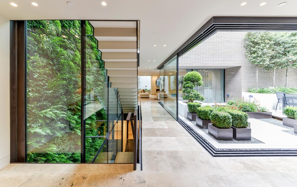 A two storey living wall follows the stairase down to the pool and gym at basement level