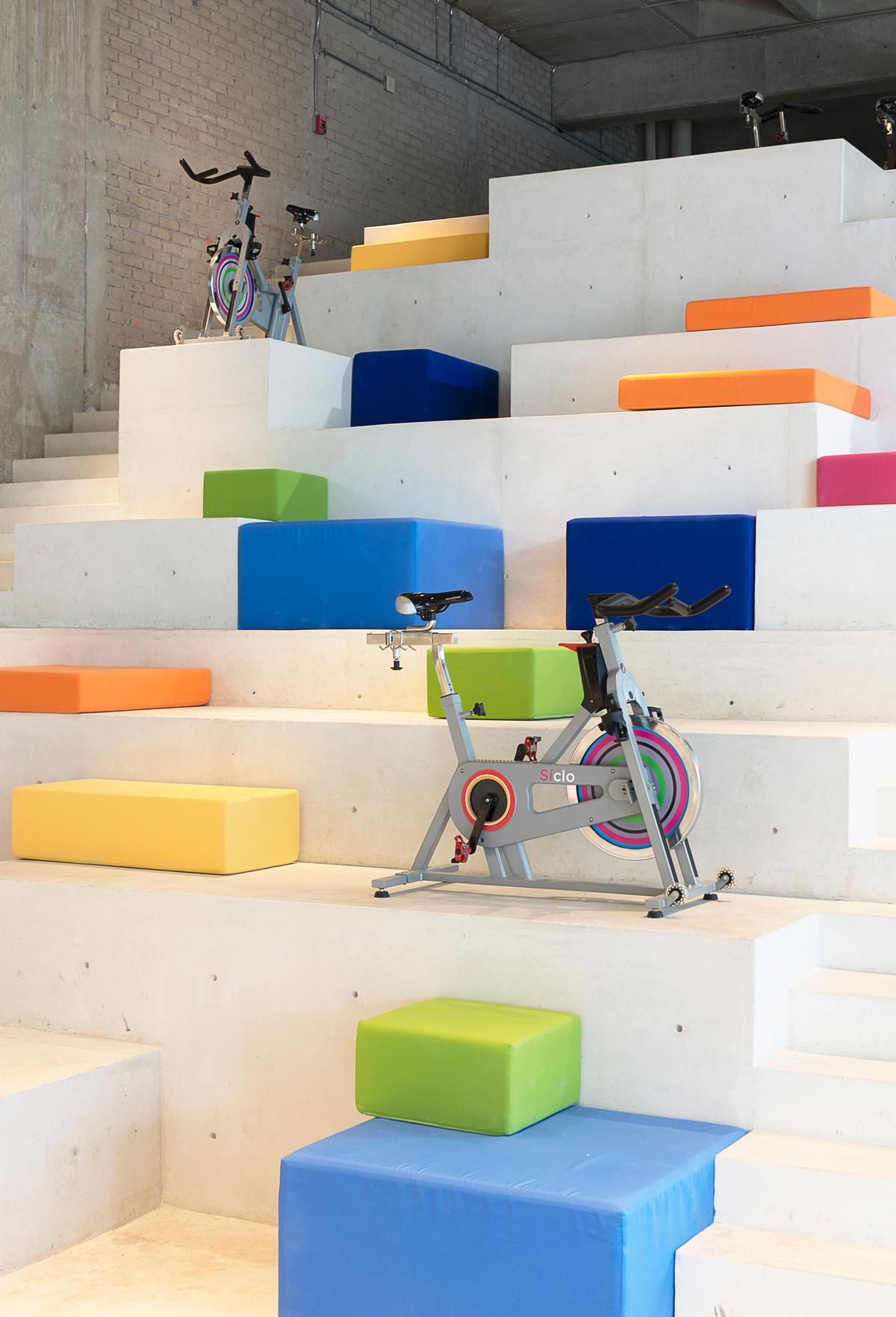 The steps of the monolith are covered with multicoloured poly-chromatic cushions and a small number of gym bikes / Jaime Navarro Soto