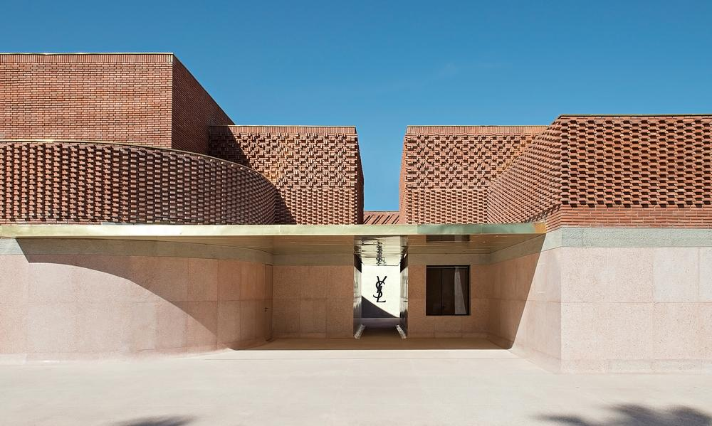 The building's façade appears as an intersection of cubes with a lace-like covering of bricks