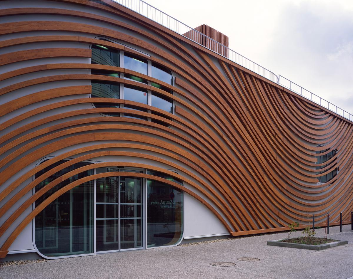 The building's external walls are clad with swirling wooden slats that recall the circular movements on the surface of water and reference to the circulation of energy and flows / Hélène Binet