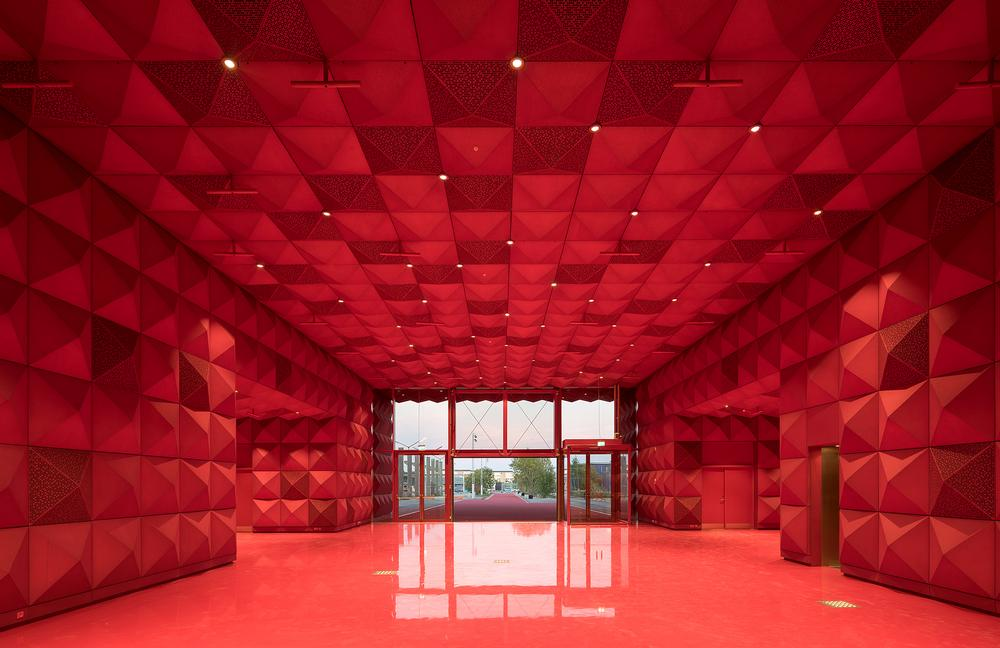 The recently opened Ragnarock rock museum in Roskilde, Denmark features a gold studded façade, bold red interiors and a cantilevered auditorium / Photos of Ragnarock: © Ossip van Duivenbode