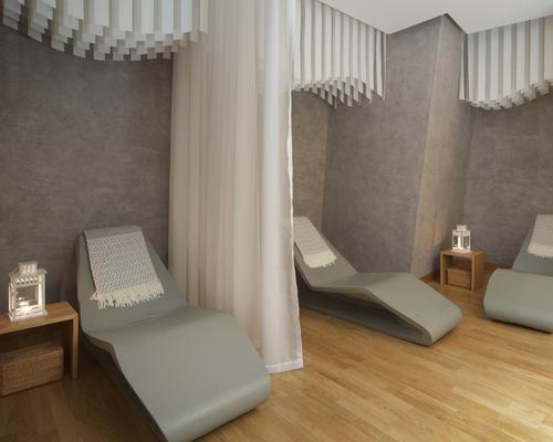 The minimalist decor in the relaxation area includes Nordic touches like soft blankets and wood fire elements