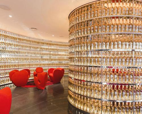 The hotel's Whisky Bar is carved into the lobby, with an undulating wall of over 2,000 custom whisky bottles featuring labels sculpted and stamped out of metal bathing the space in a bronze glow / The Watergate Hotel