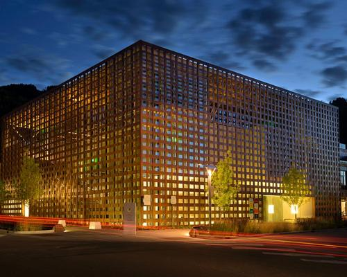 The facade is draped over the glass in the form of woven wooden cladding, made of resin and paper allowing for durability and fire resistance / Wiki Commons
