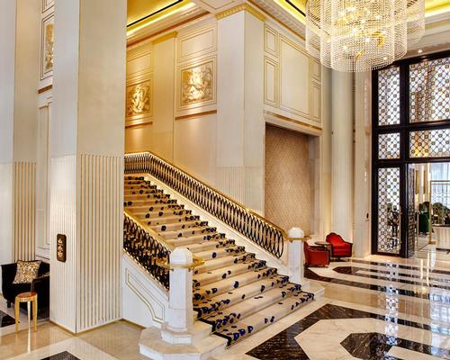The hotel's lobby features soaring ceilings and a grand staircase lit by a crystal chandelier