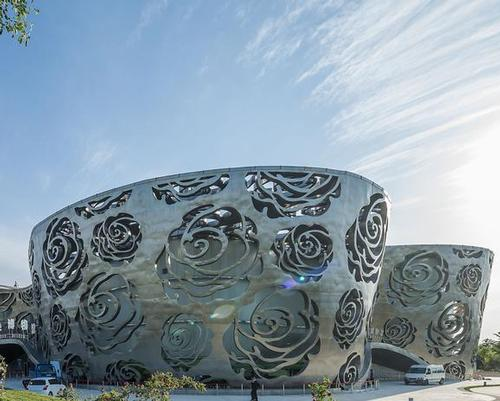 The museum is a solid volume covered by a detached silk-like skin of stainless steel with a pattern of cut-out Chinese roses / Xiao Kaixiong