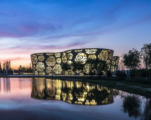 At night, the building inverts so that the roses imprinted in its skin illuminate / Xiao Kaixiong