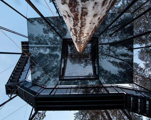 The 12x8m base of the cabin is covered with a large black and white print of trees reaching up into the sky / Johan Jansson