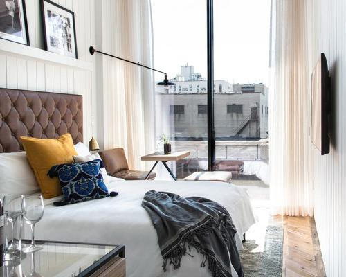 Inside, the design schemes vary from white-washed timber walls to deep grey distressed finishes with bespoke leather, brass, marble, and textured details / The Williamsburg Hotel