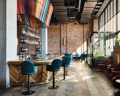 Street artist Eric Rieger has strung thousands of strands of multi-coloured yarn over the hotel bar / Annie Schlechter