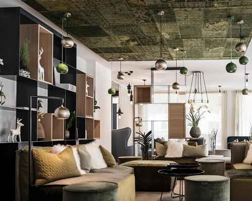 The interior design revolves around furniture and sofas in blue, green and brown tones 'that suggest alpine meadows, biotopes, moss forests or rock caves' / noa*
