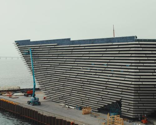 Huge cast stone panels being hung on the curving walls of Kengo Kuma's V&A Dundee; Scotland's first design museum