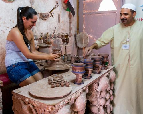 An Islamic potter teaching a female tourist making ceramic pots in Heritage villages in Abu Dhabi, United Arab Emirates