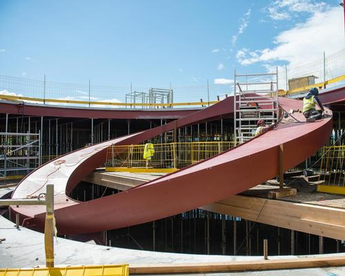 The newly released photographs show the building's circular staircase and its sinuous façade structure rising at the construction site / Luca Delachaux