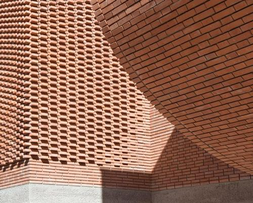 The facade appears as an intersection of cubes with a lace-like covering of bricks, which creates patterns evoking 'the weft and warp of fabric' / Nicolas Mathéus