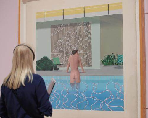 A visitor looks at <i>Peter Getting Out of Nick's Pool</i> during the David Hockney retrospective at Tate Britain in 2017, the second most popular exhibition in Tate's history