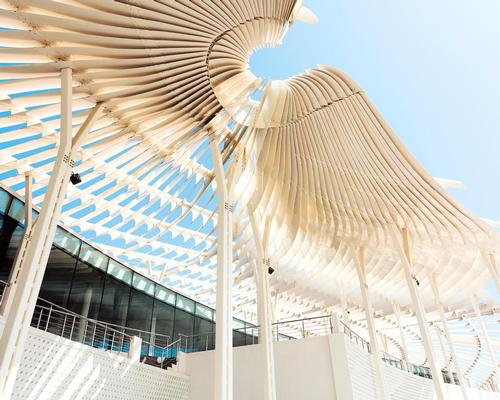 The roof canopy provides a complex counterpoint to the simple solidity of the concrete structure below / Firas Al Raisi, Luminosity Productions