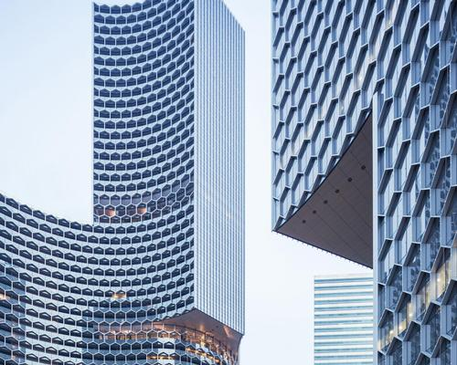 Stretched across the skin of the towers is an intricate honeycomb texture that features a series of hexagonal sunshades / Iwan Baan