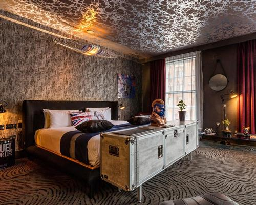 In a nod to the area's industrial heritage, walls are textured like graphite and raw concrete and floors are laid with a special 3D carpet evoking burnt rubber on asphalt / Blue Sky Hospitality