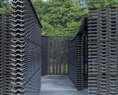 The pavilion features a black steel frame, with stacks of cement roof tiles making up the walls of the structure and a dark concrete floor / Iwan Baan