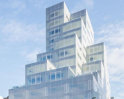 The building features pixelated steel and glass cubes that appear to float skywards / OMA