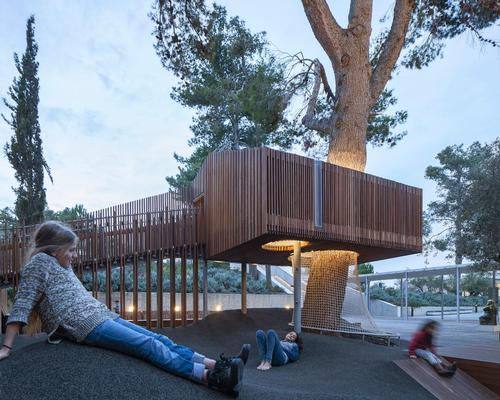 The tree house is illuminated at night / Amit Geron