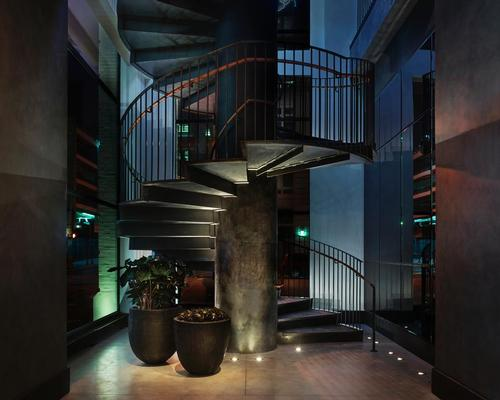 A custom-made steel cylindrical staircase links to the second floor / Design Hotels