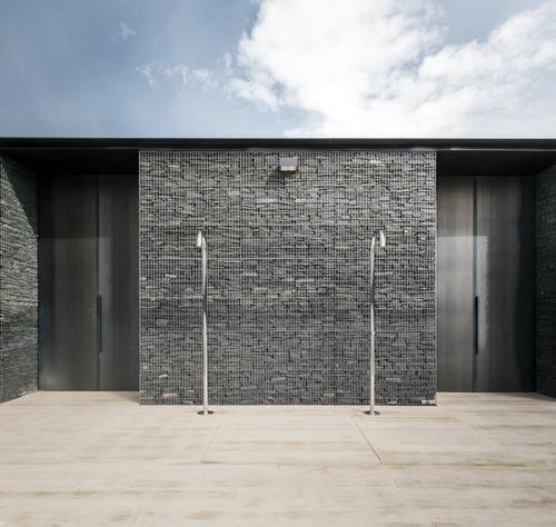 An example of the dark limestone walls behind poolside showers / gh3 architecture