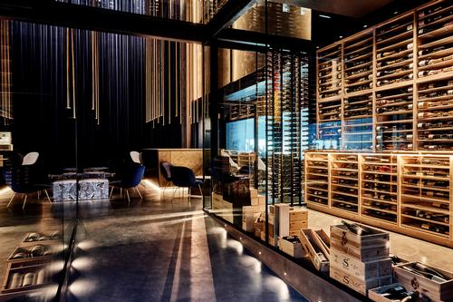 Guests move through a 10,000-bottle, three-storey wine cellar / Bech Poulsen