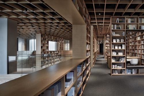 The space is both contained and shaped by wooden bookshelves / Xiangyu Sun