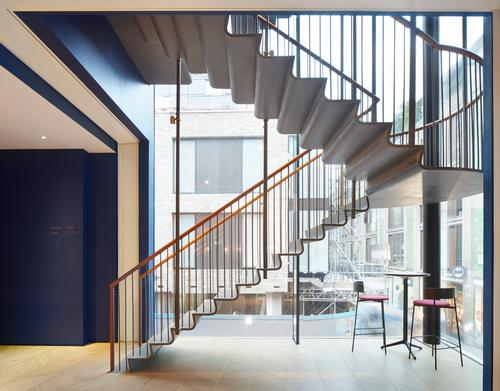 A rolled-steel feature staircase hangs in the glazed corner of one of the buildings / SODA Studio