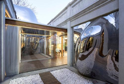 A third bubble appearas to burst through a courtyard wall / MAD Architects