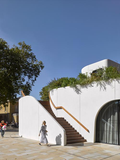 An external staircase built into the side of the structure leads to a rooftop garden / James Brittain