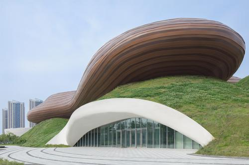 A glazed curtain wall built into the grassy hill conveys that the hill is a functional element of the design / Xia Zhi