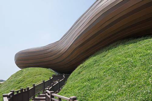 There are wooden pathways that lead visitors up the hill and underneath the upper volume of the museum / Xia Zhi
