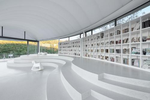 While bookshelves and tiered seating are integrated into the structure, following its curves / Jin Xiaowen