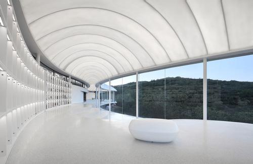 The thin roof membrane allows additional natural light into the space during the day / zystudio