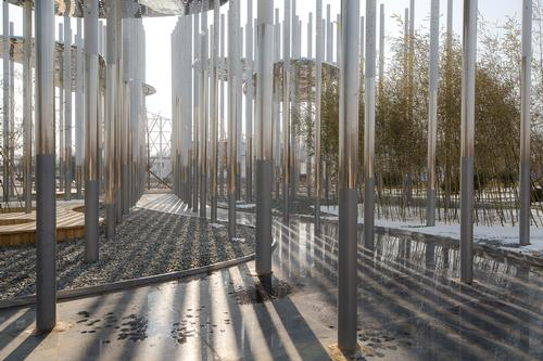 The lower sections of the poles are mirrored and undulate as one, giving the sense of a river flowing through the base of the installation / Aurelien Chen