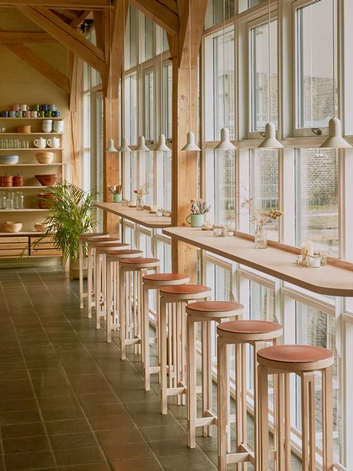 Bar seating with stools runs along the floor-to-ceiling windows on one side of the space / Vermland