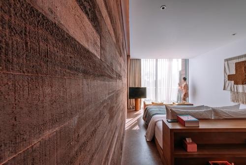 Guest rooms in the hotel feature textured concrete walls / Kevin Mak