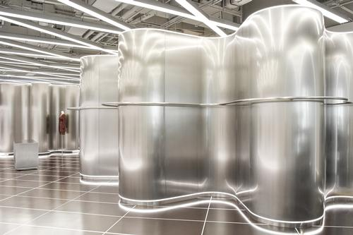 Undulating steel fixtures provide different spaces for displaying clothes / Marcella Campa