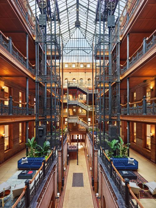 DesignAgency retained many of its original features, like the wrought iron latticework staircases, bird-cage elevators and skylights allowing natural light in / Nikolas Koenig