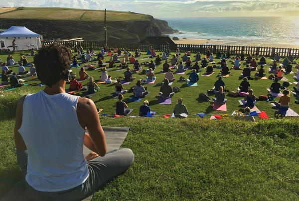 Oceanflow Yoga participants enjoying a meditation class at Bedruthan Steps  on the Cornish coast