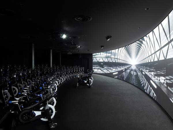 The immersive cycling studio is designed to be like a theatre, with 100 bikes and a curved screen
