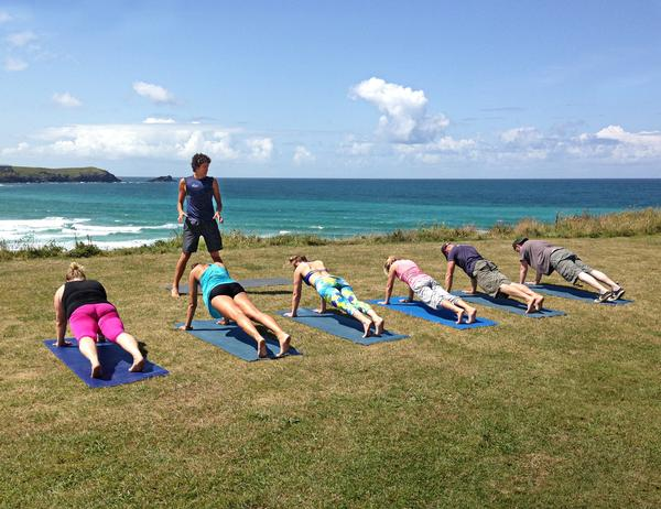 A surf yoga class overlooking the beach in Cornwall